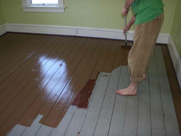 Жінка фарбує дерев'яна підлога