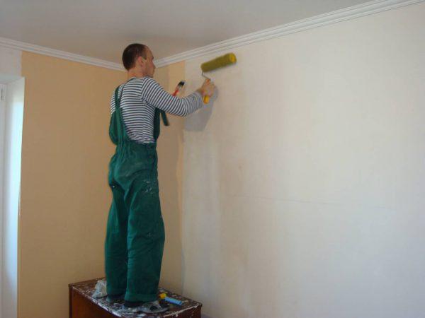 Чоловік грунтує стіни після шпаклювання