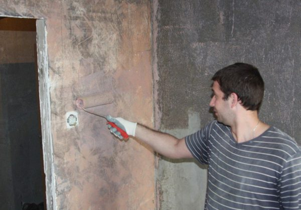 Чоловік наносить бетоноконтакт на стіну