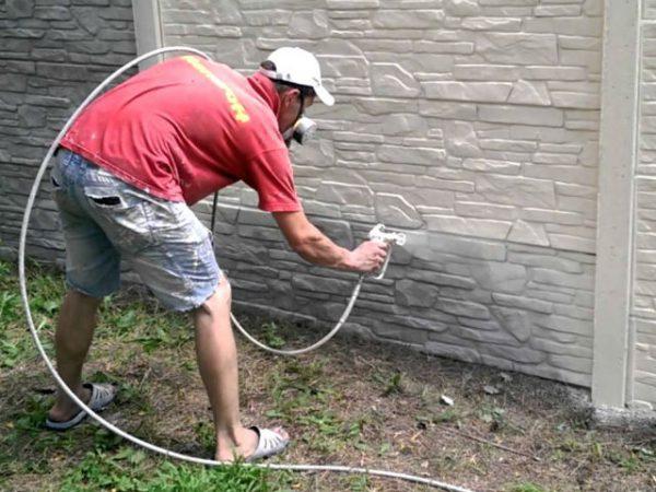 Чоловік фарбує паркан білою фарбою
