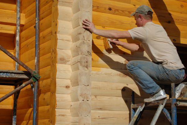 Процес фарбування стіни дерев'яного будинку