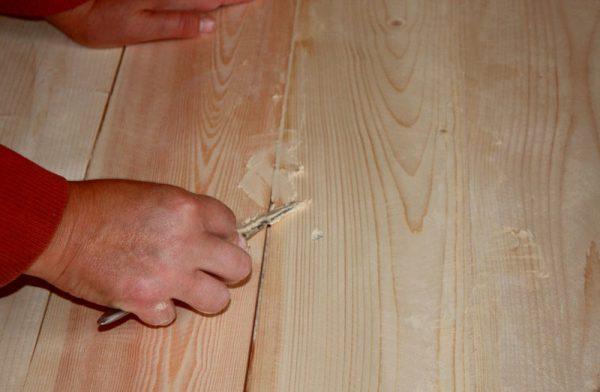 Чоловік шпаклюет дерев'яна підлога