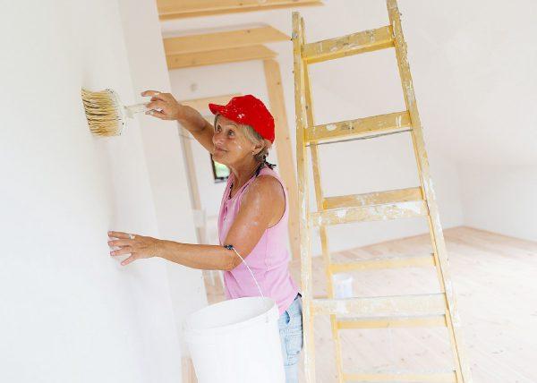 Жінка грунтує стіну
