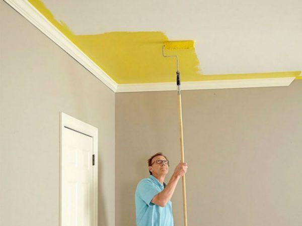 Чоловік фарбує стелю водоемульсійною фарбою